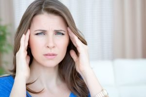 Mid-age woman suffering headache holding hands on her temples..See more LIFESTYLE images with this MID-AGE WOMAN. Click on any image below for lightbox.